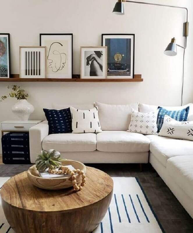 prateleira para quadros sala de estar com mesa de centro de madeira e sofá de canto Foto Jeito de Casa