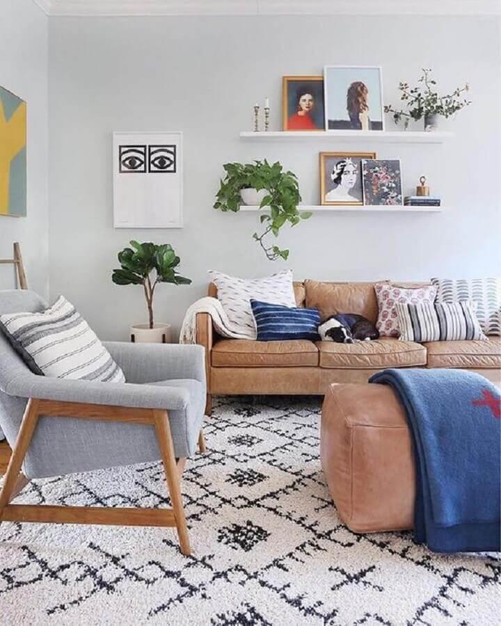 prateleira para quadros sala decorada com sofá marrom e poltrona de madeira Foto Sunny Circle Studio