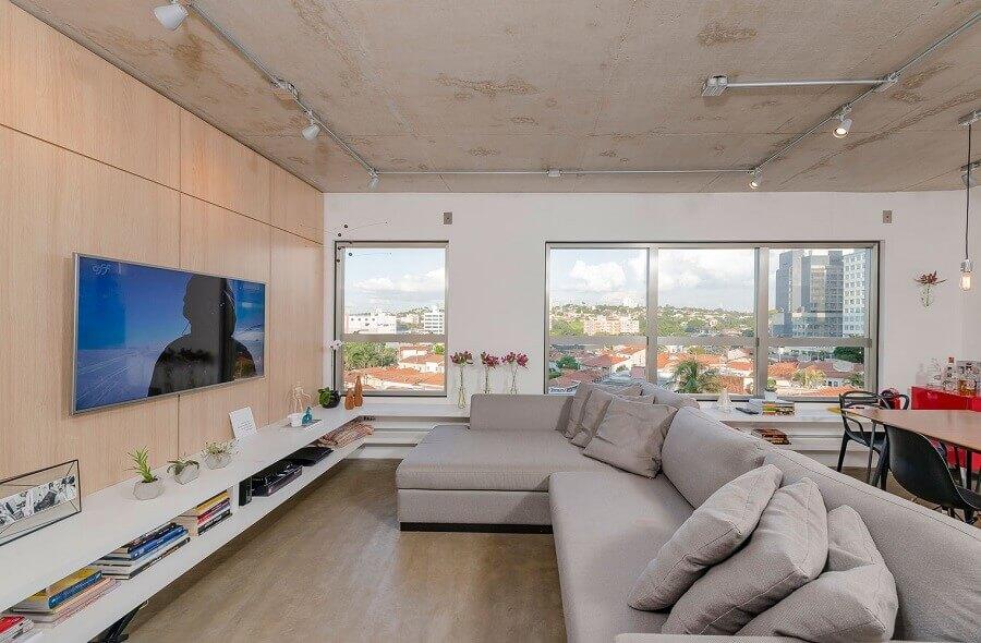 sala ampla e moderna decorada com tv na parede Foto Archdaily