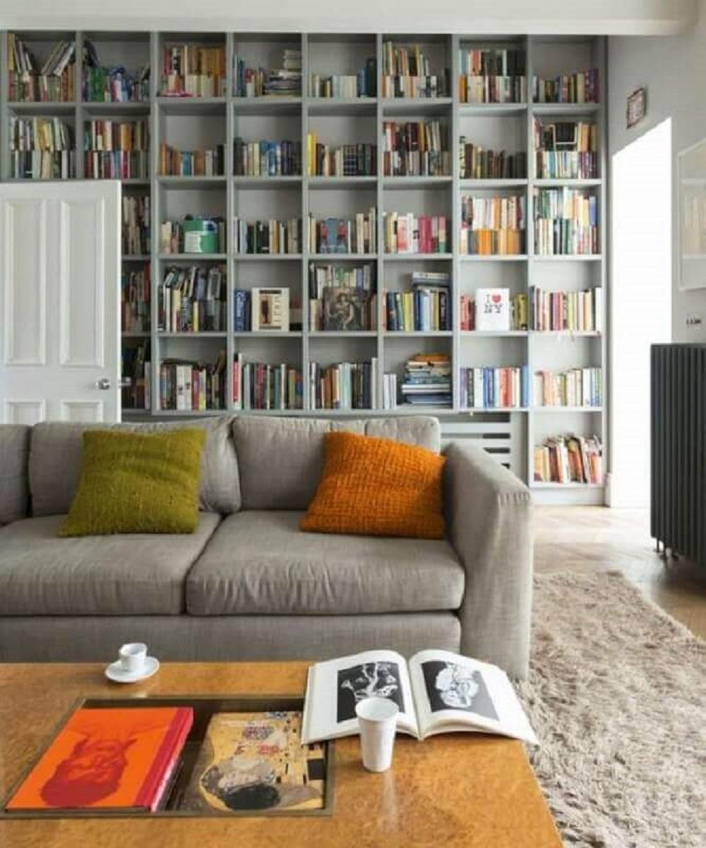 sala cinza planejada com estante de nichos para livros Foto Ideal Home