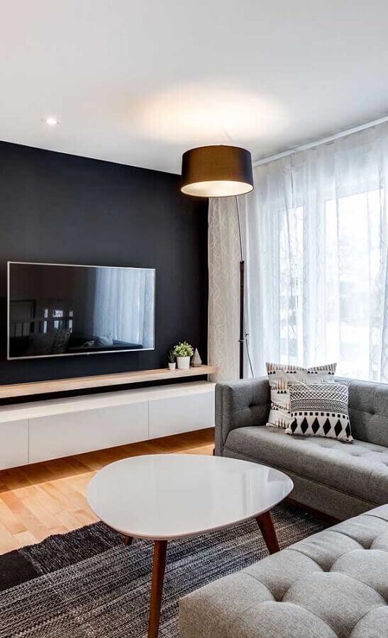 sala com TV na parede preta com rack branco suspenso Foto Home Fashion Trend