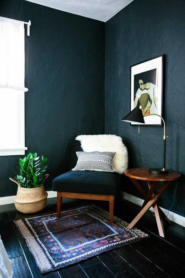sala com parede azul marinho decorado com poltrona de madeira e luminária para leitura de mesa Foto Home Fashion Trend