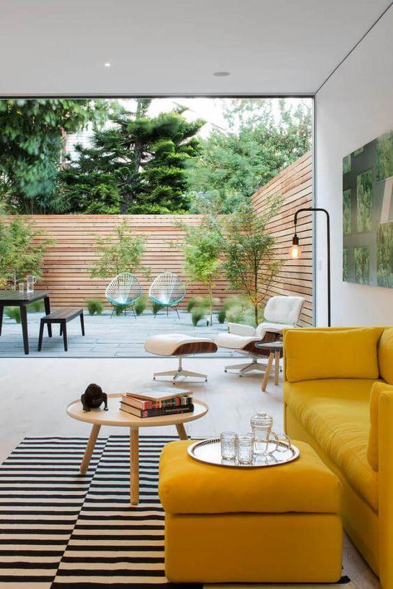 Sala com sofá amarelo e mesa pé palito de centro