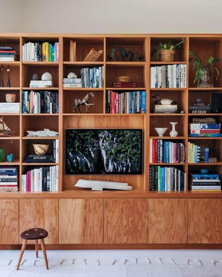 sala de tv decorada com estante de nichos de madeira Foto Martha Stewart Living