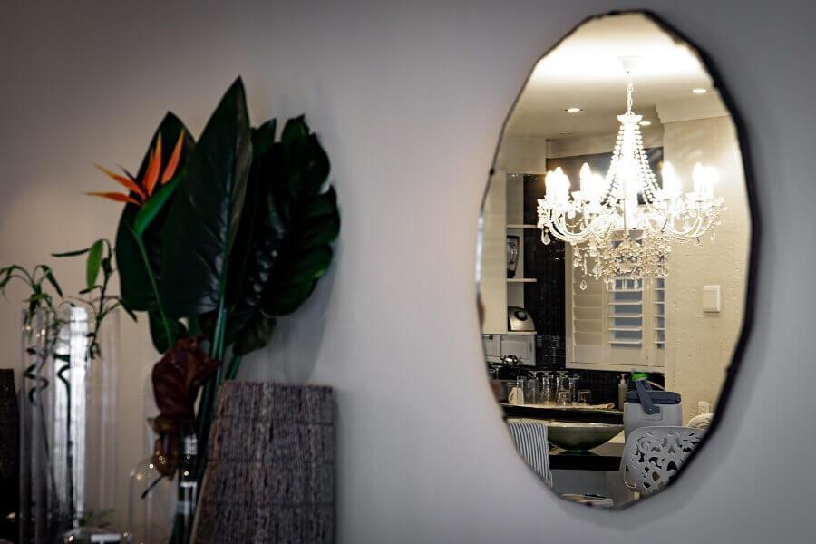 sala decorada com lustre de cristal e espelho redondo