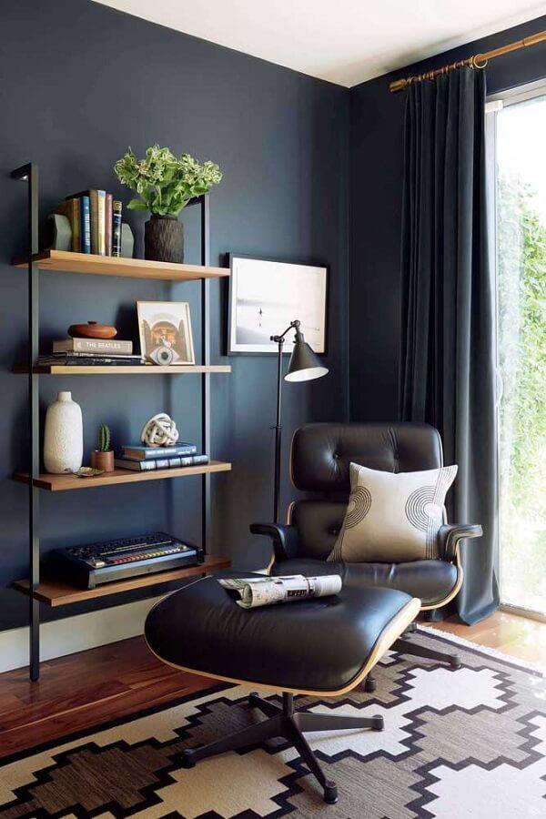 sala decorada com parede azul marinho poltrona confortável e luminária de chão para leitura Foto Pinterest