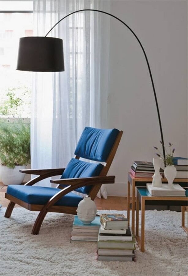 sala decorada com poltrona de madeira estofada azul e luminária de chão para leitura Foto Pinterest