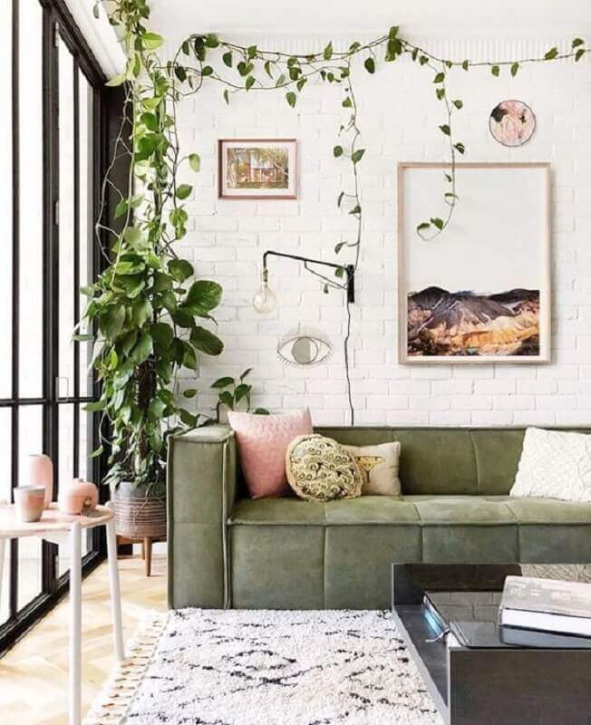 sala decorada com sofá verde e parede de tijolinho branco Foto Casa Très Chic