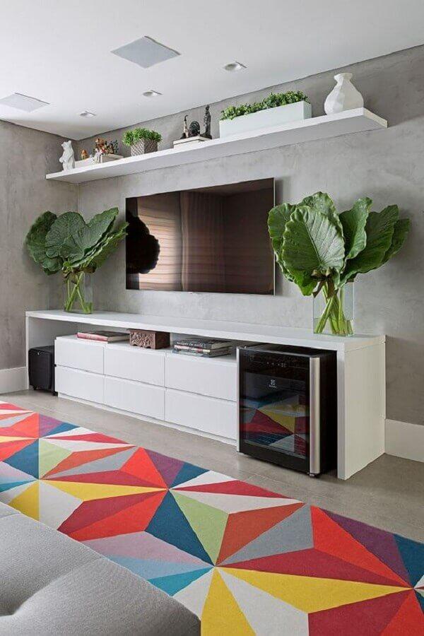 sala moderna decorada com tapete colorido e tv na parede de cimento queimado Foto Casa de Valentina