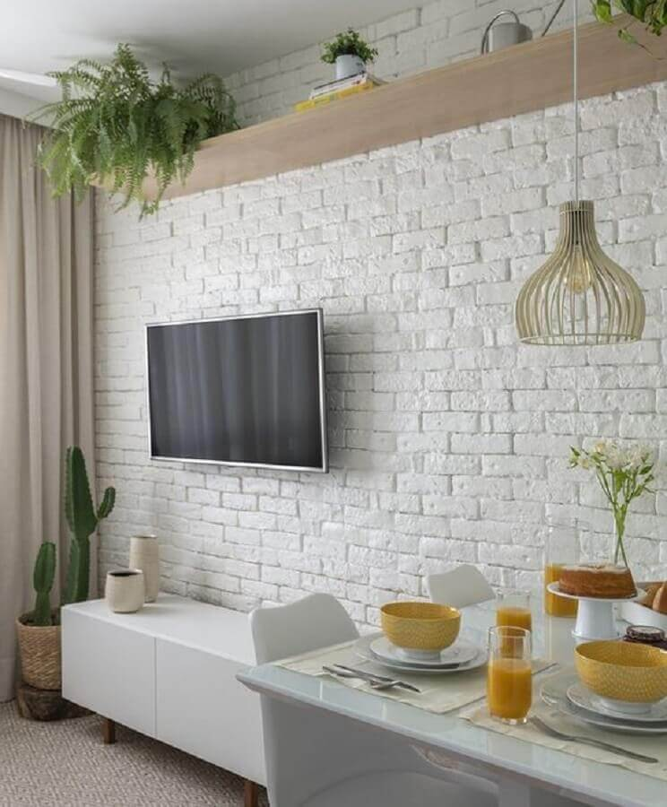 sala pequena decorada com parede de tijolinho branco Foto Jeito de Casa