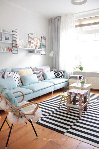 Sala retrô azul claro com tapete preto e branco