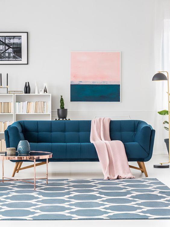 Sala retrô com sofá azul e manta rosa