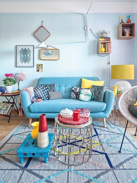 Sala retrô azul com almofadas coloridas e estampadas