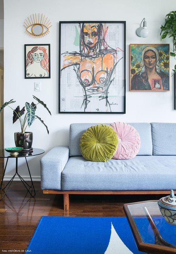 Sala retrô com sofá azul e quadros modernos