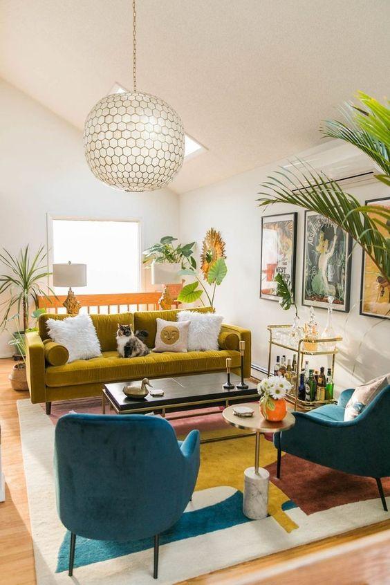 Sala retrô com sofá mostarda e poltrona turquesa
