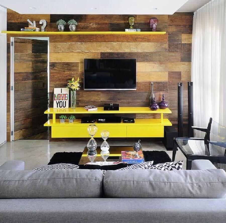 tv na parede de sala com revestimento de madeira e rack amarelo Foto Viajando no Apê