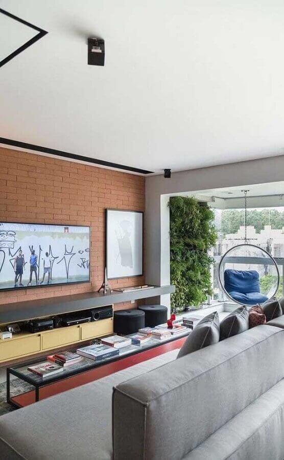 tv na parede de tijolinho à vista em sala moderna com sofá cinza Foto Futurist Architecture