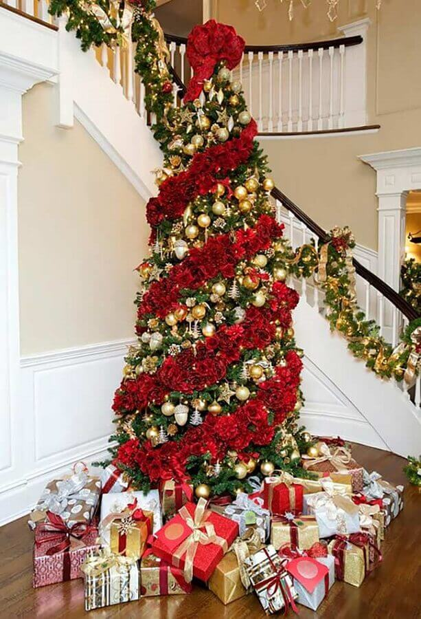 large and full Christmas tree decorated with red flowers and golden ornaments Photo Pinterest