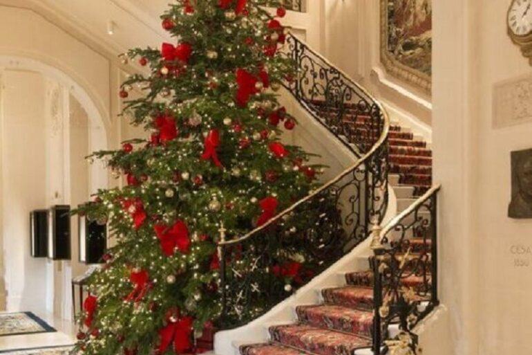 árvore de natal grande com laços vermelhos ao lado de escada Foto The Happy Hideout
