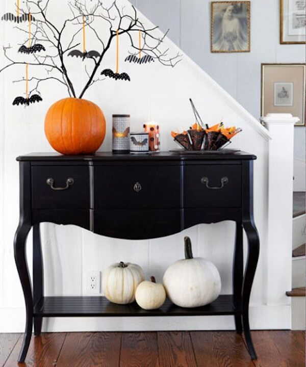 The halloween pumpkin on the black dresser serves as a pot for dried twigs