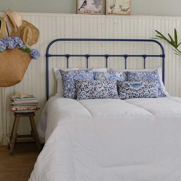 A cabeceira de cama de ferro azul se conecta com o tom das almofadas