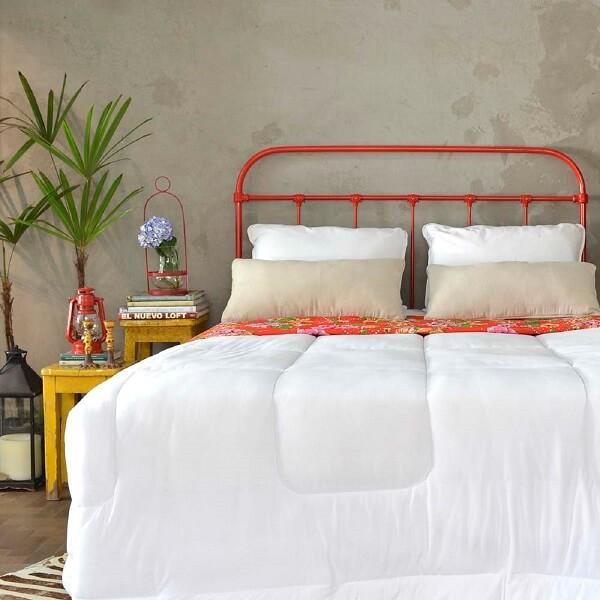 A cabeceira de cama de ferro vermelha traz um toque de cor para o dormitório