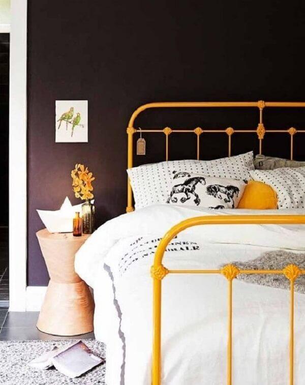 A cabeceira de ferro casal amarela ilumina a decoração do quarto
