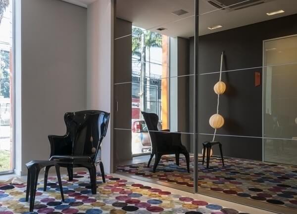 A cadeira preta se conecta com o espelho fumê do ambiente
