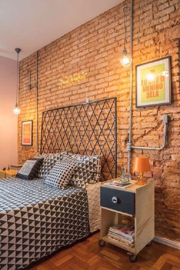 A cama com cabeceira de ferro se conecta com a parede de tijolinho aparente