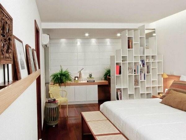A estante branca no quarto foi usada como divisória de ambientes