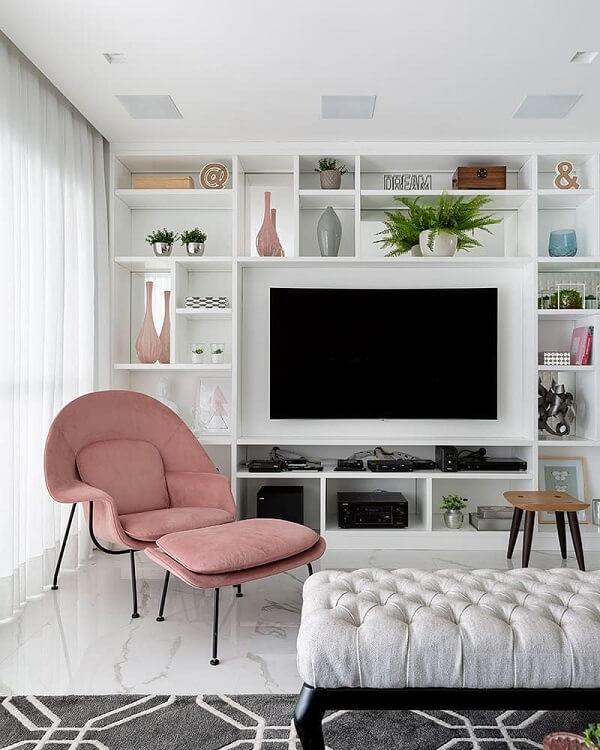 A estante branca para TV foi feita sob medida para o espaço