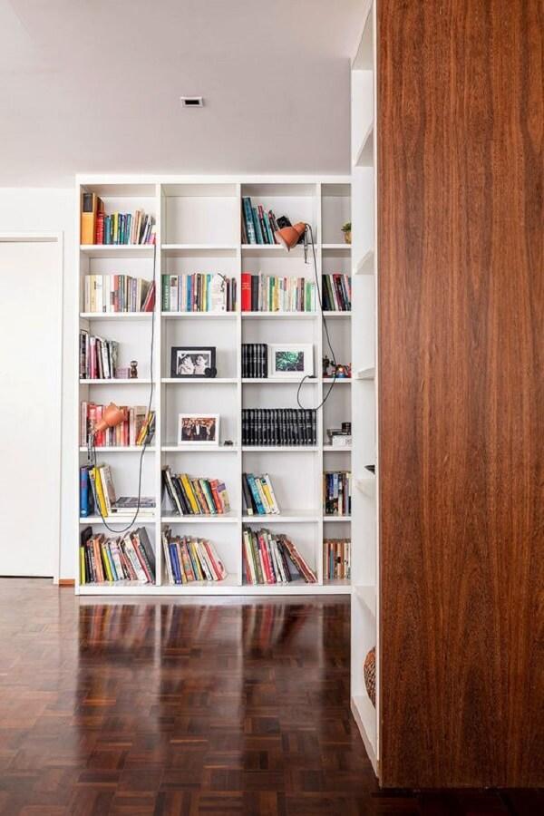A estante branca para livros auxilia na organização do ambiente