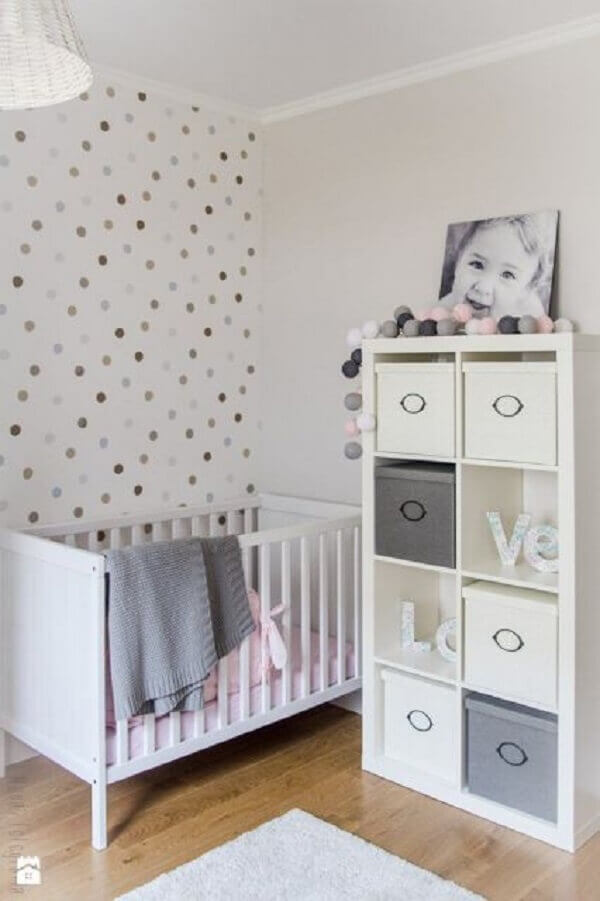 A estante branca para quarto de bebê com nichos serve de apoio para caixas organizadoras
