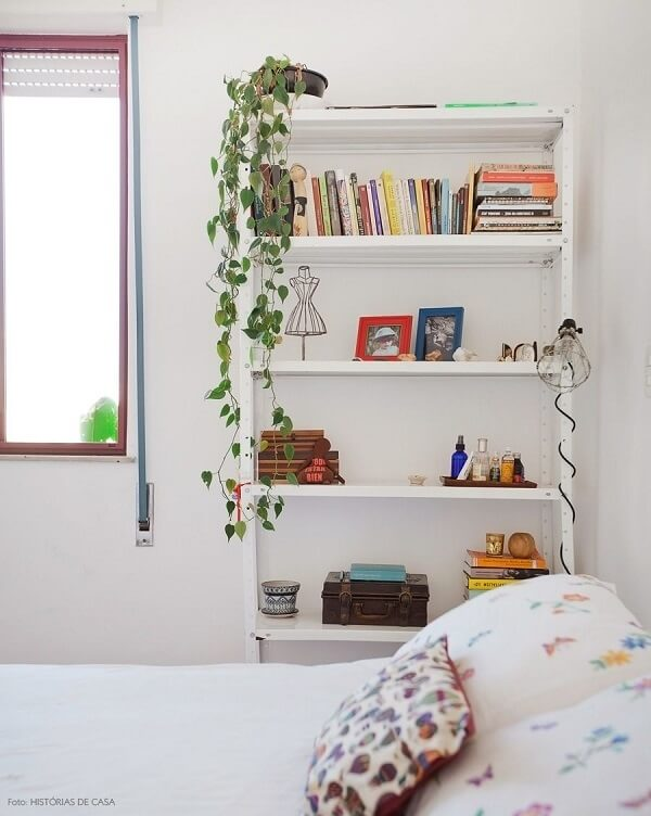 A estante de aço branca fica discreta na decoração do quarto