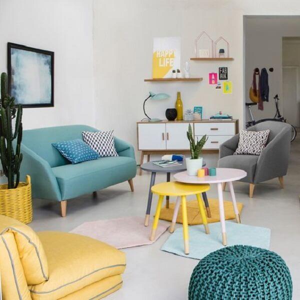 A mesa de centro retrô amarela, branca e cinza conversam com os demais móveis do ambiente