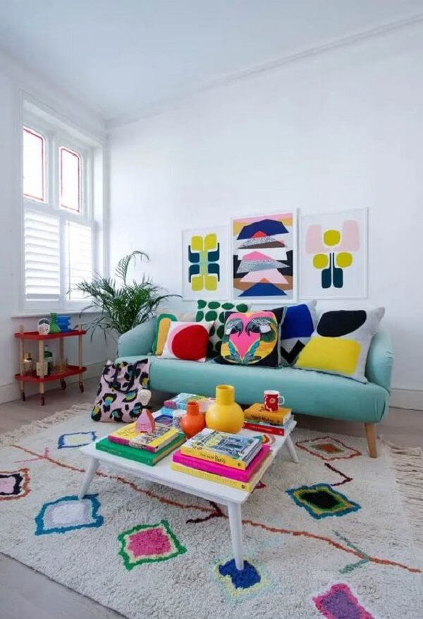 A mesa de centro retrô branca traz neutralidade para a sala colorida