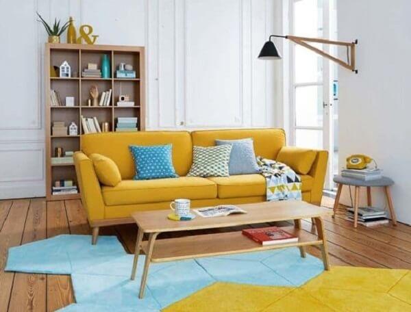 A mesa de centro retrô em madeira segue quase o mesmo comprimento que o sofá amarelo