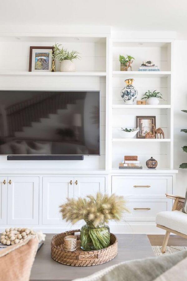 A televisão foi fixada no centro da estante home branca