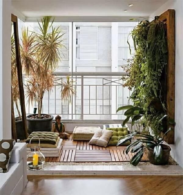Aprenda como fazer oásis em casa usando almofadas no chão, suporte para incenso, plantas, velas e um tapete