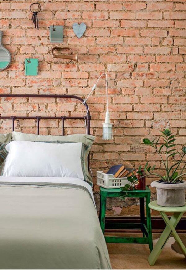 Cama com cabeceira de ferro e parede de tijolinho aparente formam uma combinação perfeita