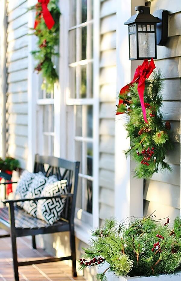 Outdoor garden Christmas decoration with red branches and ties