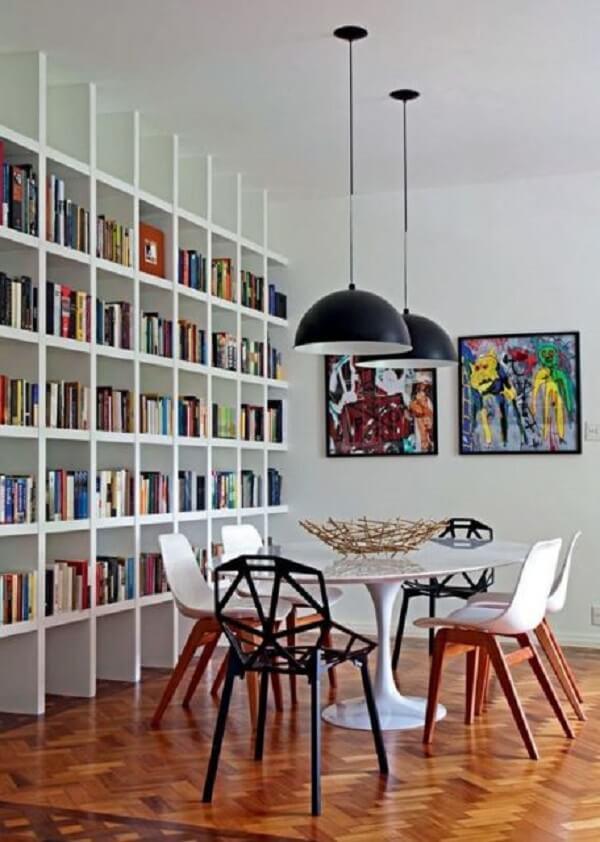 Diversas obras foram organizadas nessa estante branca para livros