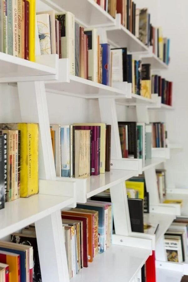 Estante branca para livros organizados em grupos semelhantes