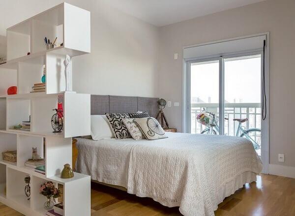 Estante branca para quarto de casal utilizada como divisória de ambiente