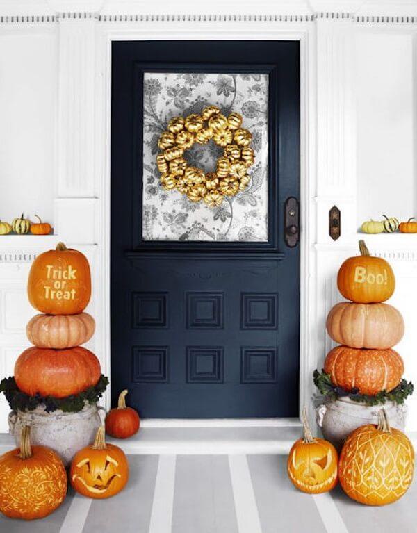 Guirlanda with mini halloween pumpkin painted in gold decorate the front door