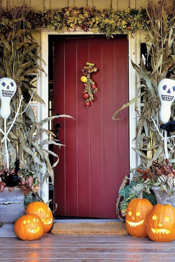 Many dried leaves and halloween pumpkins decorate the front of the house