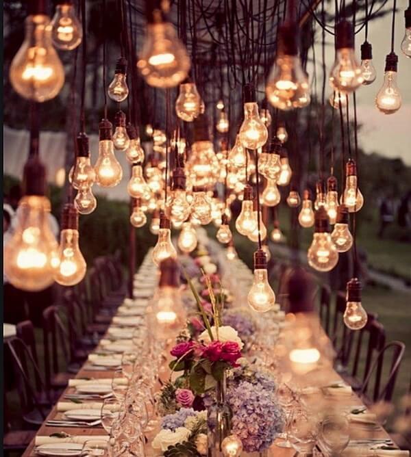 O cordão de luz de lâmpadas decoram toda a extensão da mesa de casamento