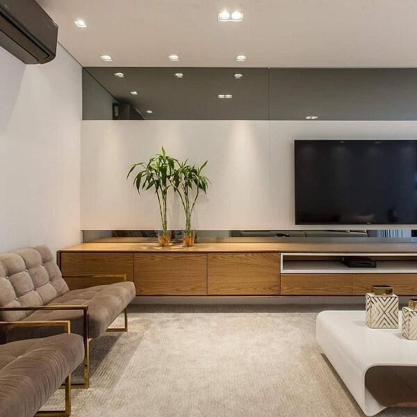 O espelho fumê na sala acima da tv cria um efeito especial