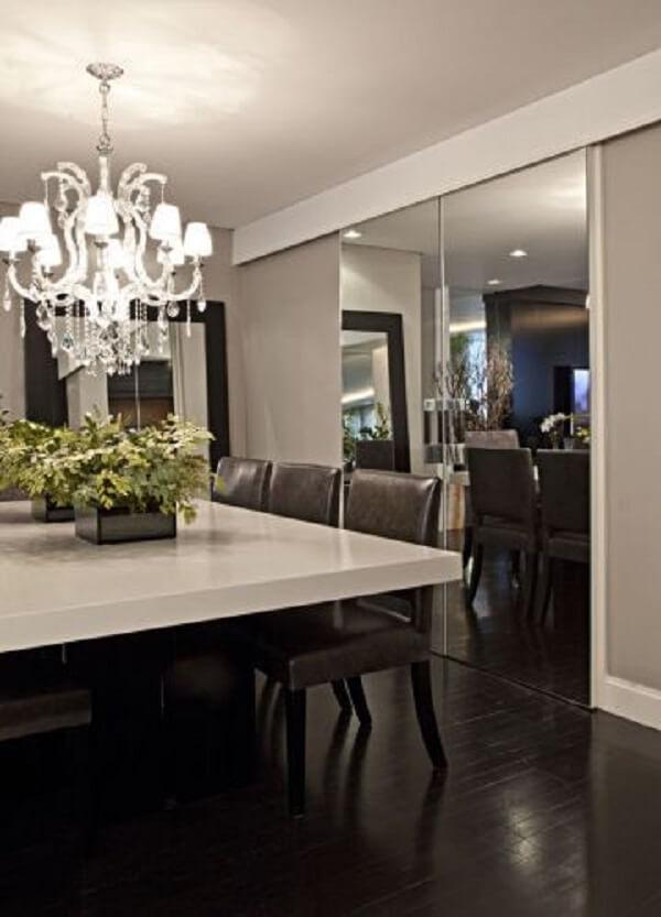 O espelho fumê na sala de jantar traz a sensação de amplitude