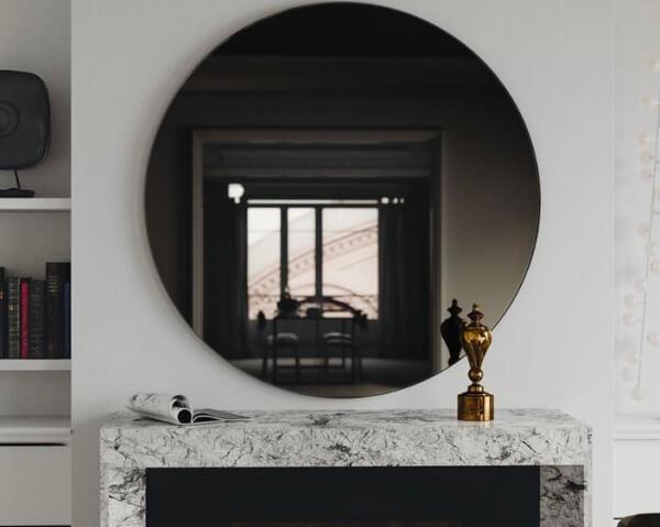 O espelho fumê redondo é o grande destaque dessa decoração